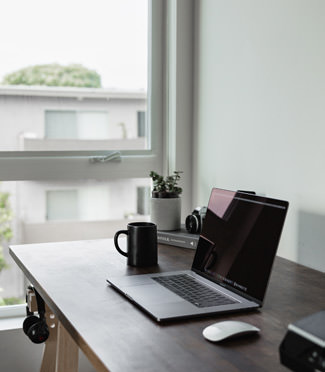 Computer on desk by an open window