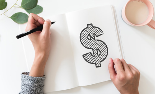 Hands drawing dollar sign in notebook